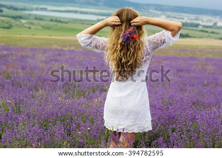 Back view of girl at purple lavender field - stock photo