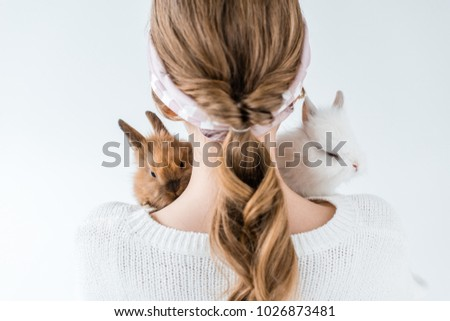 back view of girl holding adorable furry bunnies isolated on white
