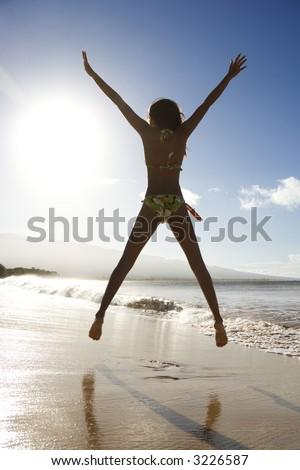 Back view of girl in bikini jumping enthusiastically on beach in Maui, Hawaii, USA. - stock photo