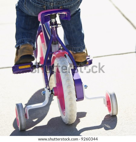 Back view of girl riding bicycle with training wheels. - stock photo