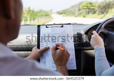 back view of girl taking driving test  - stock photo