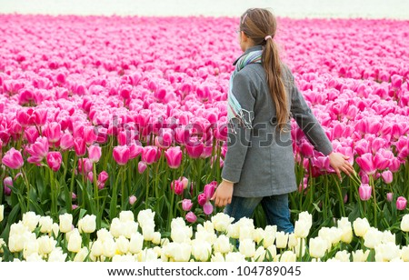 Back view of girl walks between of the purple tulips field