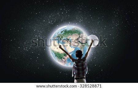Back view of girl with hands up looking at planets. Elements of this image are furnished by NASA - stock photo