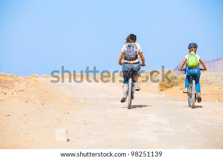 Back view of girl with her mother having a weekend excursion on their bikes on a summer day in beautiful landscape - stock photo