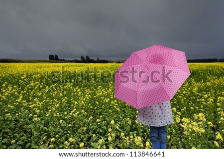 back view of girl with umbrella outdoors in the rain - stock photo
