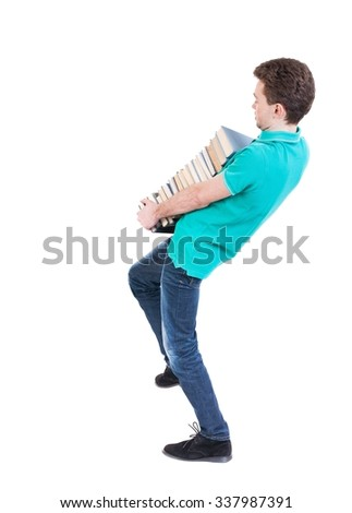 Back view of going  handsome man carries a stack of books. walking young guy . Rear view people collection.  backside view of person.  Isolated over white background. Man corrects foot stack of books - stock photo