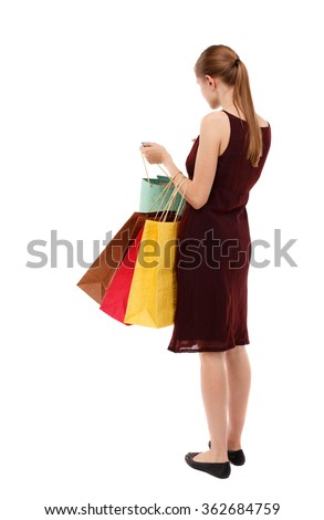 back view of going  woman  in  dress woman with shopping bags . beautiful brunette girl in motion.   Isolated over white background. Girl in a brown dress standing looking at their purchases in bags. - stock photo