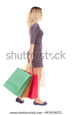 back view of going  woman  with shopping bags . beautiful brunette girl in motion.  backside view of person.  Isolated over white background. girl in the purple dress is left with bags - stock photo