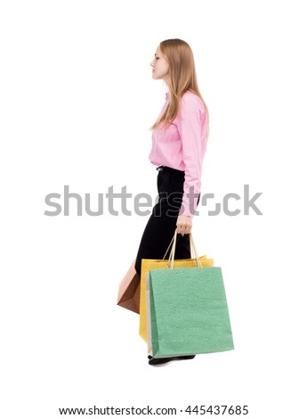 back view of going  woman  with shopping bags . beautiful girl in motion.  backside view of person.  Rear view people collection.  The girl in the pink shirt is bent under the weight of the bags. - stock photo