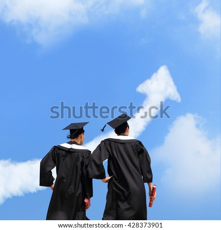 Back view of graduates student look arrow cloud in blue sky and think future - stock photo
