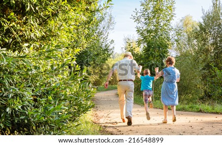 Back view of grandparents and grandchild jumping on a nature path - stock photo