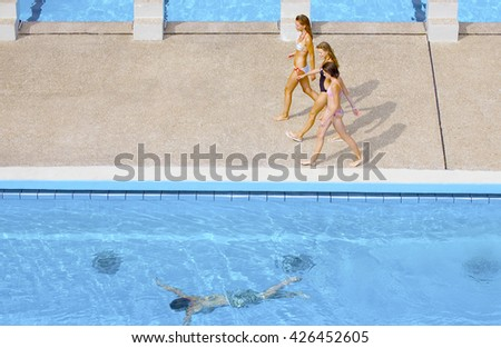 Back view of Group Of Teenage Friends Having Fun at Swimming Pool