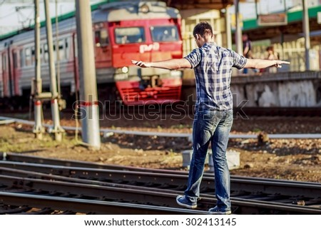 Back view of handsome dark-haired young man walking on the rails keeping his balance against the railway station background. Image with selective focus - stock photo