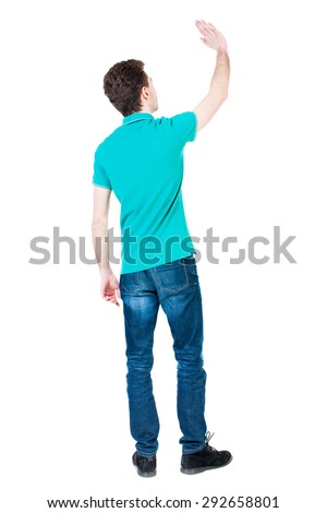 Back view of handsome man greeting waving from his hands. Standing young guy in jeans. Rear view people collection. The guy in a stylish T-shirt aquamarine waves up his hand in farewell. - stock photo