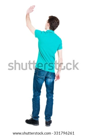 Back view of handsome man greeting waving from his hands. Standing young guy in jeans. Rear view people collection.  backside view of person.  Isolated over white background.  - stock photo