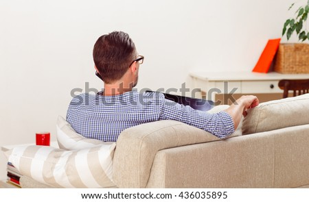 Back view of handsome man in glasses speaking over mobile or smart phone while lying on sofa or couch with laptop computer at home.