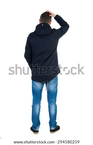 Back view of handsome man in winter jacket  looking up.   Standing young guy in parka. Rear view people collection.  backside view of person.  I Man in warm jacket scratching top of the head arm. - stock photo