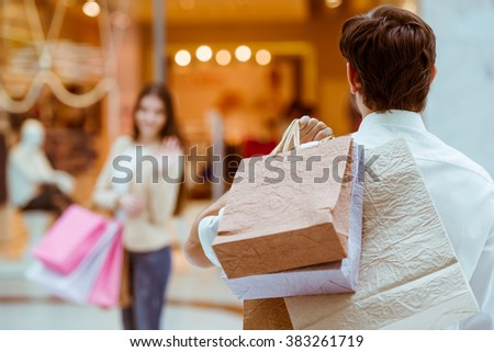 Back view of handsome man meeting his beautiful woman in mall. Both holding shopping bags - stock photo