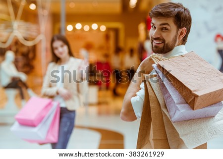 Back view of handsome man meeting his beautiful woman in mall. Both holding shopping bags. Focus on man - stock photo