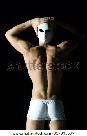 Back view of handsome sexual young man with straight body and beautiful bottom in white underwear holding white mask near head standing in studio on black background, vertical picture - stock photo