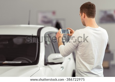 Back view of handsome young man making a photo of car using smart phone while standing in a motor show - stock photo
