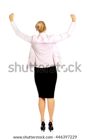 Back view of happy business woman with arms up - stock photo