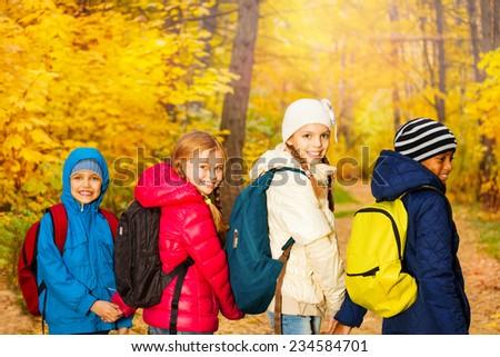 Back view of happy children wearing rucksacks - stock photo