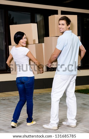 Back view of happy couple carrying cardboard containers while moving to new house - stock photo