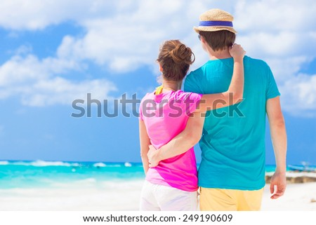 back view of happy couple in sunglasses on the beach - stock photo