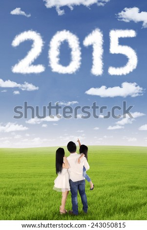 Back view of happy family standing on the meadow while looking numbers 2015 on the sky - stock photo