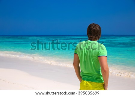 back view of happy man enjoying good life on exotic beach, guy looking on seaside, tropical island background. Travel concept. - stock photo