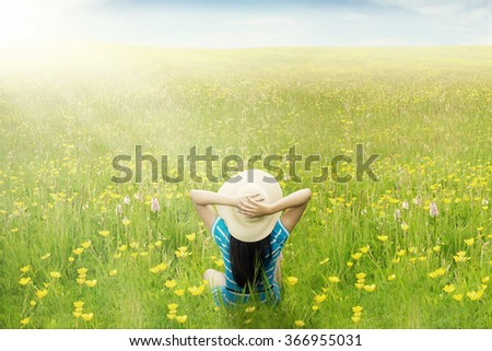Back view of happy woman relaxing on the green meadow while sitting and enjoy blossom flowers at springtime - stock photo
