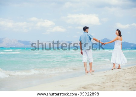 Back view of happy young couple have fun on a deserted tropical beach with bright clear blue sky