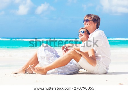 back view of happy young couple in white on the beach - stock photo