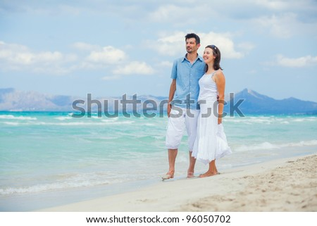 Back view of happy young couple walking on a deserted tropical beach with bright clear blue sky - stock photo