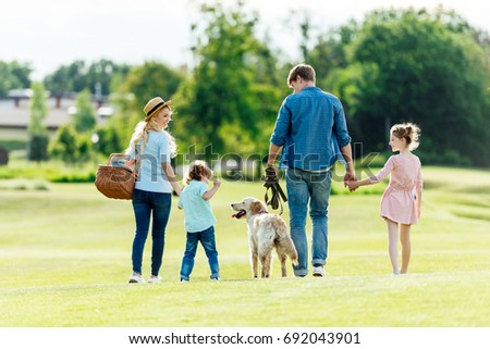 back view of happy young family with pet walking on green meadow at park