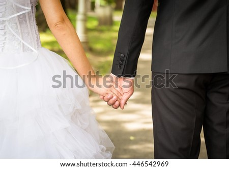 Back view of holding hands couple in love, bride and groom outdoor walking in a park