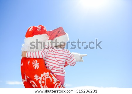 Back view of joyful excited little kid hugging Santa Claus over blue sky outdoors background