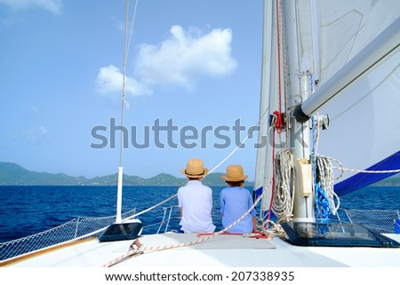 Back view of kids enjoying sailing on a luxury catamaran or yacht - stock photo