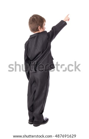 back view of little boy in business suit pointing at something isolated on white background