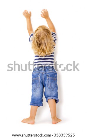 Back view of little boy with hands up on white background.  - stock photo