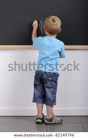 back view of little boy writing on a blackboard - stock photo