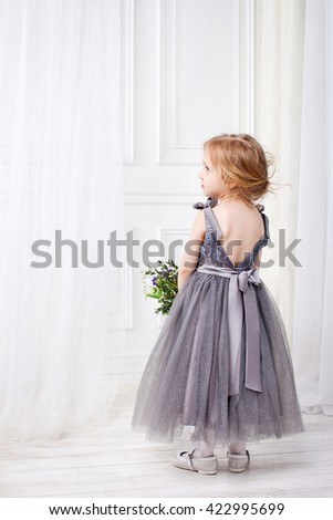 Back view of little girl llooking aside. Rear view. Little girl in beautiful festive dress from a decollete on a back - stock photo