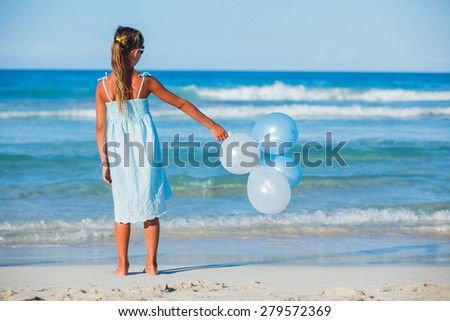 Back view of little girl with bunch of ballons on the beach - stock photo