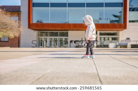 Back view of little girl with hoodie looking her new sneakers in a city square on a sunny day - stock photo