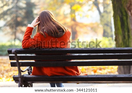 Back view of lonely young brunette woman sitting on a bench in the park - stock photo