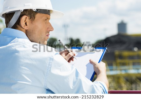 Back view of male architect with clipboard at construction site - stock photo