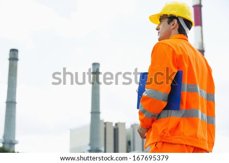 Back view of male architect with clipboard standing at site - stock photo