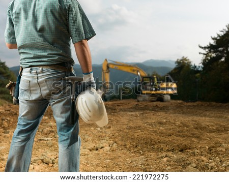 back view of male engineer standing on construction site holding white hardhat - stock photo
