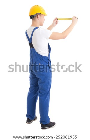 back view of man builder in blue uniform holding measure tape isolated on white background - stock photo
